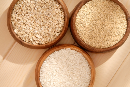 meagre: Some oatmeal, millet, rice are in woody bowls  Stock Photo