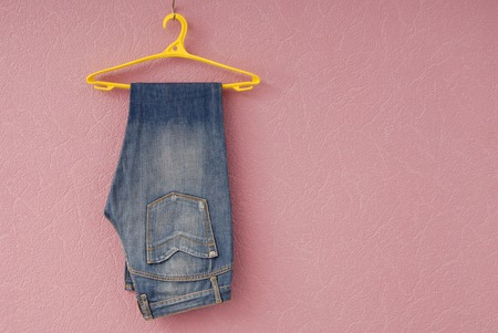 blue jeans are on yellow hanger