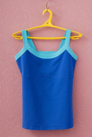 light blue lingerie: sports tee shirt is on yellow clothes-hanger Stock Photo