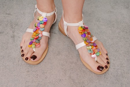 leather sandals are on female feet photo
