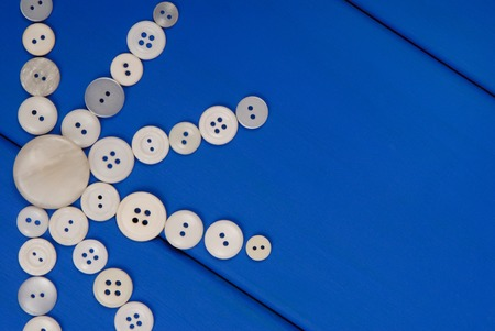 plastik: white buttons are on blue wooden background, sun pattern Stock Photo