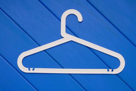 clotheshanger: white plastic hanger in on blue wooden floor Stock Photo