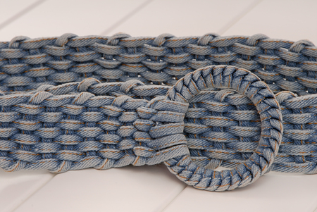 spliced: blue denim textile belt is on the white show-case Stock Photo