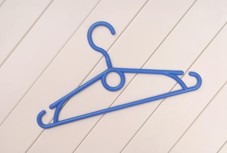 clotheshanger: Blue plastic coat-hanger is on white