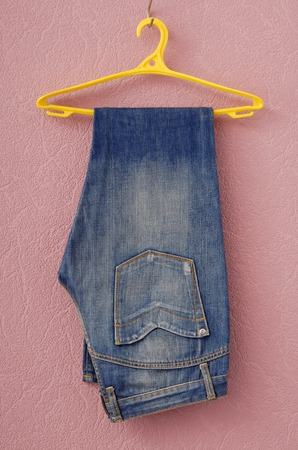 clotheshanger: blue contemporary jeans are on yellow clothes-hanger