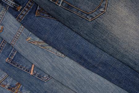 denim background: blue denim background, pile of different jeans, back side
