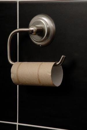 black bathroom: tube is on metal holder,  toilet paper is in black bathroom