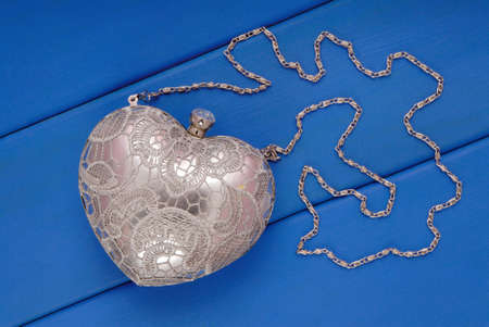 silvery: metal evening handbag with chain, clutch has heart shape, handbag is on blue