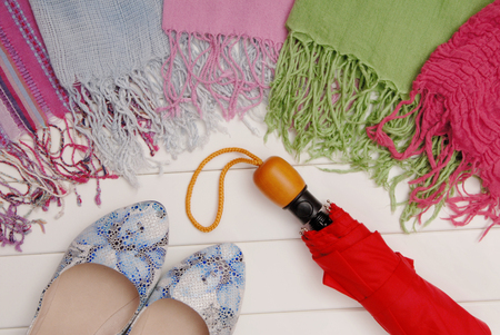 assortment of female accessories,  scarfs, red umbrella and blue shoes are on shop window