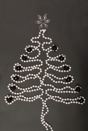 symbolic  New Years tree, New-year tree, white beads are on black background, post card