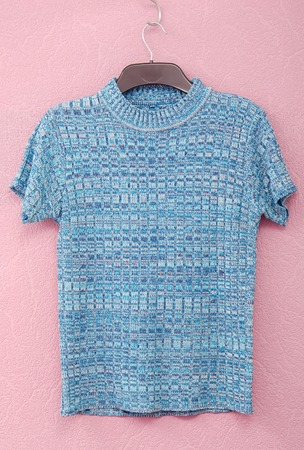 blue blouse is on lilac background, blue sweater with short sleeve,  a sleeveless top has aqua colour