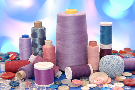 spools of thread and buttons  are on artistic many-colored background Stock Photo