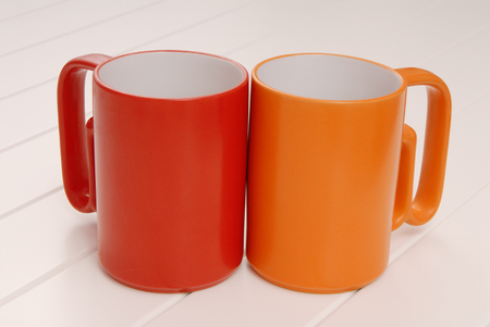 empty orange and red mugs; modern colored mugs; empty cups for drinks are; in the kitchen; couple of cups are on white background Stock Photo