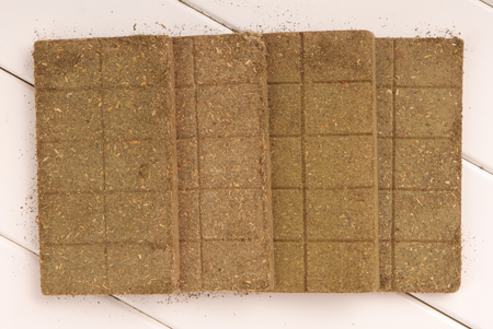 bricks of herb, briquettes of herb, bar of herb, herbal bars, briquettes of  nettle,  desiccated leaves, desiccated leaves of nettle, dried nettle, bars of desiccated leaves of nettle Stock Photo