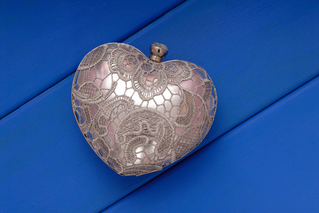 metal evening handbag, clutch has heart shape, handbag is on blue table, symbol of Saint Valentines Day, metal grey clutch in  show-window,