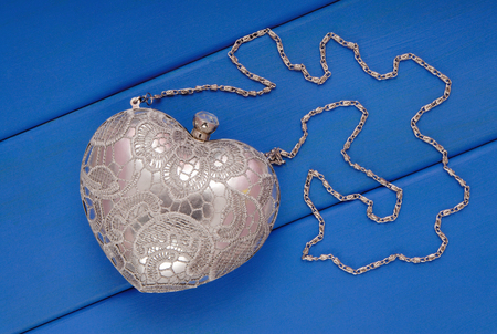metal evening handbag with chain, clutch has heart shape, handbag is on blue