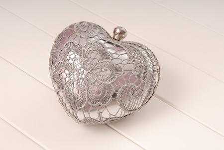 metal evening handbag, clutch has heart shape, handbag is on white background, sparkly, silvery grey handbag