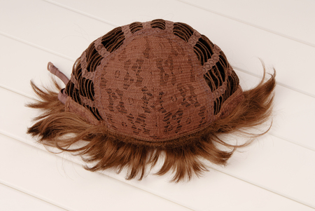 backside of brown wig, inside, the internal side of wig, curly hair is on white table Stock fotó