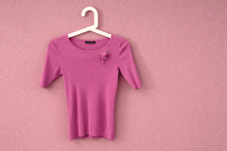 lilac blouse is on a wall, female tee shirt is on pink background, T-shirt is a single object, jersey clothing, texturing lilac backgrounds and empty space; Stock Photo