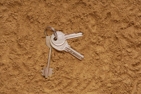 lost keys are on the sand, find keys are on the ground, key are as a clue, metal keys are on the texturing backgrounds