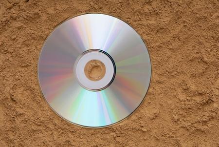 Il CD è sulla sabbia, il CD-ROM è a terra, il disco è su una spiaggia, il disco CD-ROM è su uno sfondo strutturato, il DVD è sulla terra, musica perduta, trova ispirazione, Archivio Fotografico