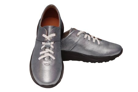 leather blue footwear, shine sneakers with white laces, grey trainers are on white background, fashionable boots are isolated, silver-colored female sports shoes, silvery trendy gym shoes 免版税图像