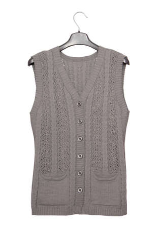 gray knitted vest, warm clothing for the elderly, isolated woolen sleeveless is on white background, female waistcoat with pockets, autumn clothes is on clothes-hanger