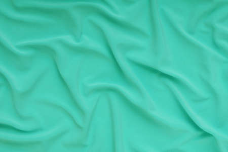 textile light green background, cloth as creative backdrop, beautiful draped bright material, abstract drape lime material, turquise color of fabric 免版税图像