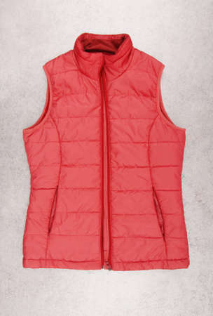 warm red waistcoat is on gray background, rose vest as single object, unisex sleeveless jacket, isolated beautiful outerwear, spring pink down jacket on white, nobody 免版税图像