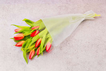 bouquet of red tulips in the package, flowers in plastic wrap, romantic gift in cellophane on gray table, packed beautiful present on floor 免版税图像