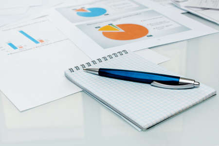 Notepad with pen and financial papers with graphs. oncept of management and planning in company. Banking, accounting and Finance.