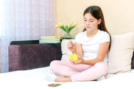 ute young caucasian girl deposit coin into piggy bank for future life sitting on sofa in living room at home 版權商用圖片
