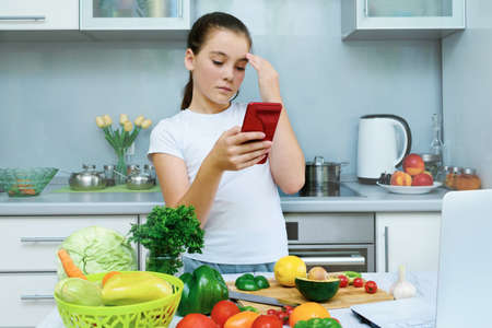 Beautiful young girl cooking in kitchen and looking for recipe on telefon. Laptop on kitchen table. Food blogger concept