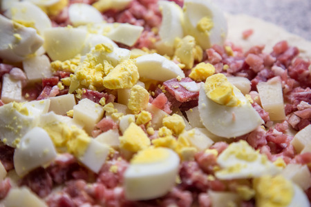 Eggs, Salami and Bacon mixed together during the preparation of a salty cake. Concept of homemade food and cooking activity, ingredient.