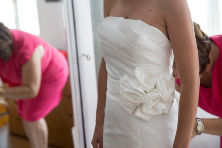 bottons: Detail of a Bridal wedding dress with the brides mother on the background Stock Photo