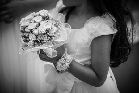 Detail of a child bridesmaid with a small bouquet in her hands