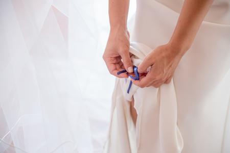 Bride putting a traditional blue ribbon as a garter on her leg, detail Standard-Bild
