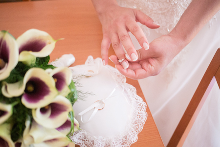 Hands detail with bride putting the engagement ring on the other hand Stock Photo