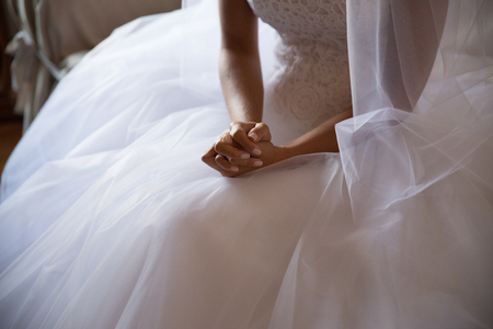 Bride's hands detail with wedding dress