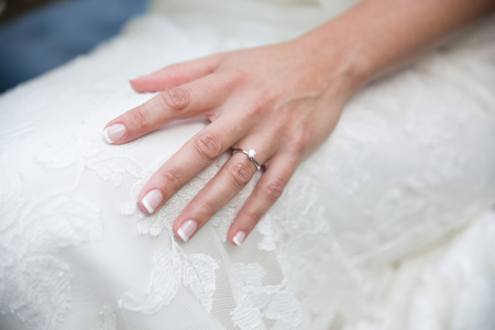 Bride's hand detail with wedding dress and engagement ring Standard-Bild