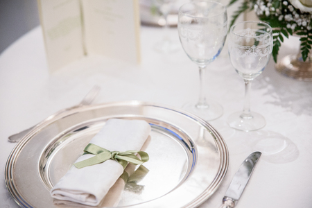 Elegant restaurant table with silver plate and decorations.