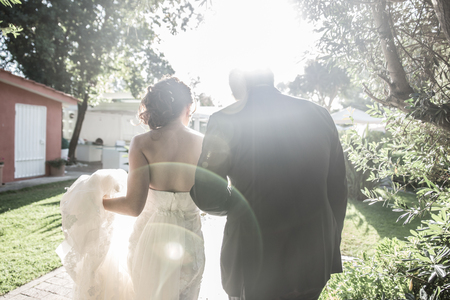 Bride and groom walking in a beautiful garden, with sunlight