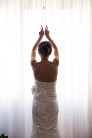 Bride opening the window curtains