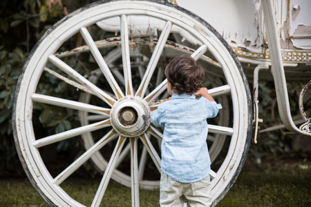 Child playing with a wheel of an old carriage
