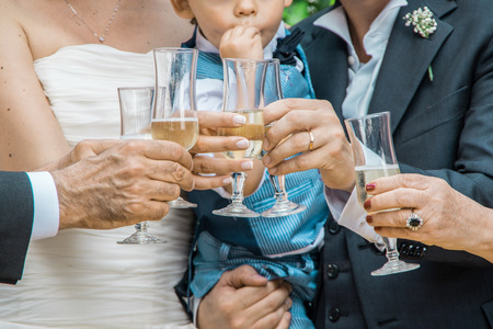 Bride and groom with their baby at their wedding, making a toast with champagne