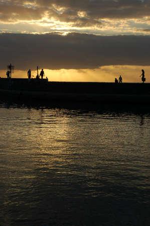 Silouhette of people walking on a pier at Runion Island