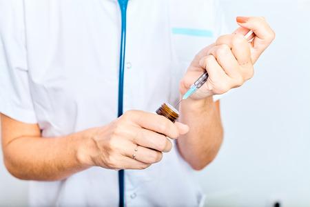 Woman doctor filling medicine from ampule into syringe. Reklamní fotografie