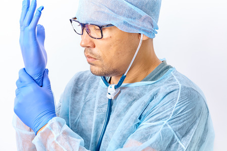 Handsome young doctor with a stethoscope around the neck putting on rubber gloves in hospital or clinic
