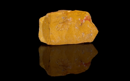 Jasper yellow  raw mineral stones with reflection on black background photo