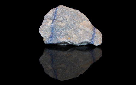 Aventurine blue raw mineral stones with reflection on black background